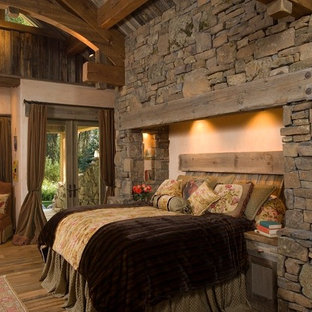 Mountain style master medium tone wood floor bedroom photo in Other with beige walls