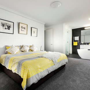 This is an example of a large contemporary loft-style bedroom in Perth with white walls, carpet and black floor.