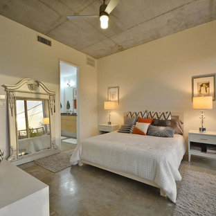 Example of a trendy master concrete floor bedroom design in Austin with white walls and no fireplace