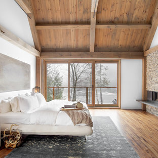This is an example of an expansive contemporary master bedroom in Montreal with white walls, medium hardwood floors, a standard fireplace and a metal fireplace surround.