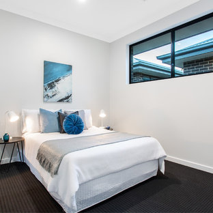 This is an example of a modern bedroom in Adelaide with grey walls, carpet and black floor.