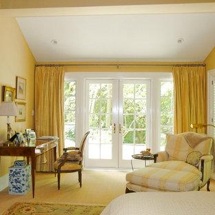 Ejemplo de dormitorio principal, clásico, grande, con paredes amarillas, moqueta, chimenea tradicional y marco de chimenea de piedra