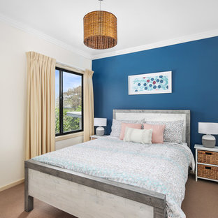 Inspiration for a mid-sized beach style guest bedroom in Melbourne with blue walls, carpet, no fireplace and brown floor.