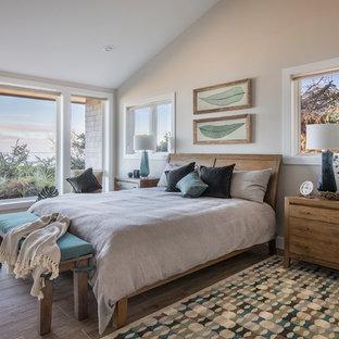 Bedroom - mid-sized beach style master porcelain floor and brown floor bedroom idea in Portland with beige walls