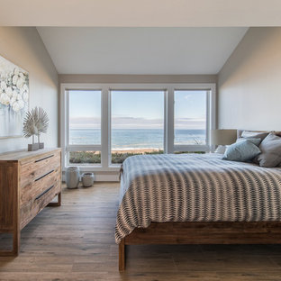 Inspiration for a mid-sized beach style guest porcelain floor and brown floor bedroom remodel in Portland with beige walls