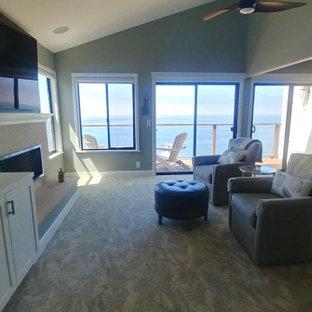 Aménagement d'une grand chambre bord de mer avec une cheminée ribbon, un manteau de cheminée en pierre de parement et un plafond voûté.