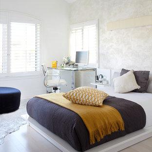 Cette photo montre une chambre d'amis tendance de taille moyenne avec un mur multicolore, un sol en bois clair, aucune cheminée et un sol gris.