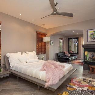 サンディエゴの大きい地中海スタイルのおしゃれな主寝室 (グレーの壁、セラミックタイルの床、コーナー設置型暖炉、コンクリートの暖炉まわり、茶色い床) のインテリア