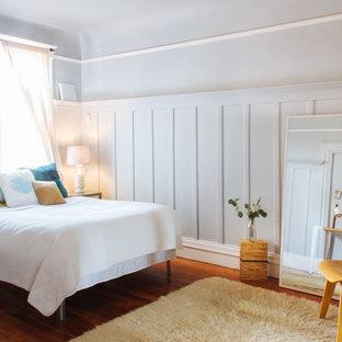 Immagine di una camera matrimoniale classica di medie dimensioni con pavimento in legno massello medio, nessun camino, pareti blu e pavimento arancione