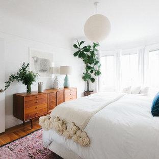 Exemple d'une chambre parentale rétro de taille moyenne avec un mur blanc, un sol en bois brun, aucune cheminée et un sol marron.