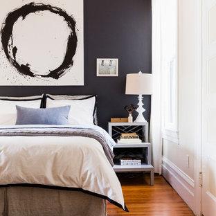 Exemple d'une chambre parentale chic avec un mur noir et un sol en bois brun.