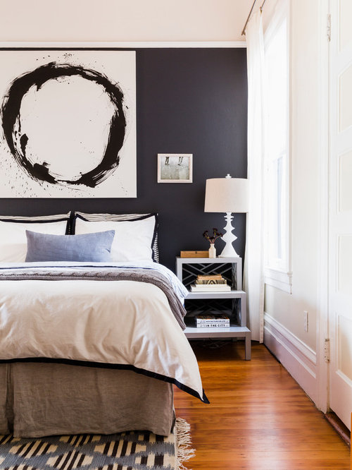 Inspiration for a transitional master medium tone wood floor bedroom  remodel in San Francisco with black