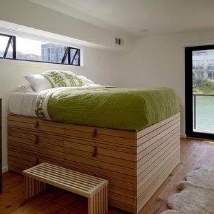 Diseño de dormitorio moderno con paredes blancas y suelo de madera en tonos medios