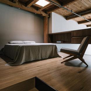 Industrial loft-style bedroom in San Francisco with beige walls and medium hardwood floors.