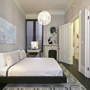 Example of a trendy dark wood floor bedroom design in San Francisco with gray walls and a standard fireplace