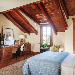 Ispirazione per una camera da letto tradizionale con pareti beige, pavimento in legno massello medio e pavimento marrone