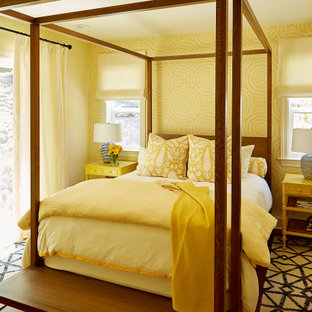 Mid-sized eclectic master bedroom in San Francisco with yellow walls, medium hardwood floors, no fireplace, brown floor and wallpaper.