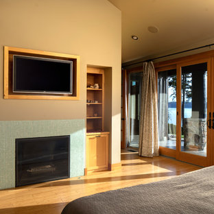 Example of a mid-sized eclectic master bamboo floor and brown floor bedroom design in Seattle with beige walls, a standard fireplace and a tile fireplace
