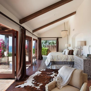 Example of a tuscan master terra-cotta tile bedroom design in Santa Barbara with white walls