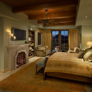 Example of a large tuscan master travertine floor bedroom design in Phoenix with green walls, a standard fireplace and a stone fireplace