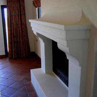 На фото: с высоким бюджетом хозяйские спальни среднего размера в средиземноморском стиле с белыми стенами, полом из терракотовой плитки, стандартным камином и красным полом