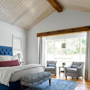 Modelo de dormitorio principal, de estilo de casa de campo, con paredes blancas y suelo de madera en tonos medios
