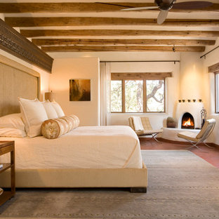 Inspiration for a large southwestern master bedroom remodel in Albuquerque with beige walls, a corner fireplace and a plaster fireplace