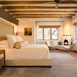 Неиссякаемый источник вдохновения для домашнего уюта: большая хозяйская спальня с бежевыми стенами, угловым камином и фасадом камина из штукатурки