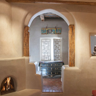 Inspiration for a large mediterranean master brick floor and red floor bedroom remodel in Albuquerque with beige walls