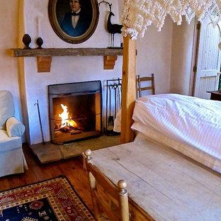Foto de dormitorio principal, rústico, de tamaño medio, con paredes beige, suelo de madera en tonos medios, chimenea tradicional y marco de chimenea de yeso