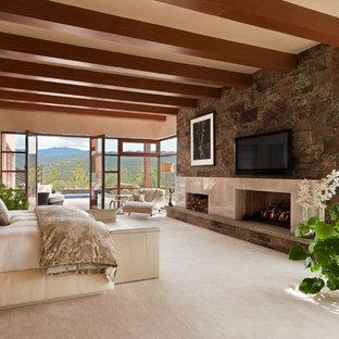 アルバカーキの巨大なサンタフェスタイルのおしゃれな主寝室 (ベージュの壁、カーペット敷き、標準型暖炉、石材の暖炉まわり) のレイアウト