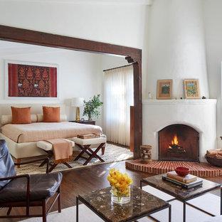 Cette image montre une chambre parentale méditerranéenne avec un mur blanc, une cheminée d'angle, un manteau de cheminée en plâtre, un sol marron et un sol en bois foncé.