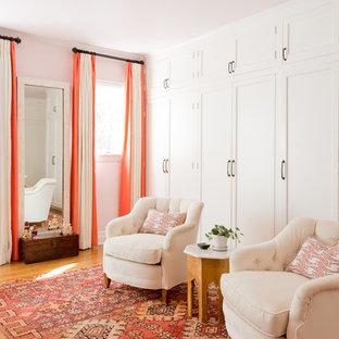 Aménagement d'une grande chambre parentale éclectique avec un sol en bois brun, un mur rose, aucune cheminée et un sol marron.