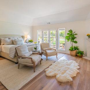 На фото: большая хозяйская спальня в стиле кантри с белыми стенами, паркетным полом среднего тона, стандартным камином, фасадом камина из камня, сводчатым потолком и коричневым полом с