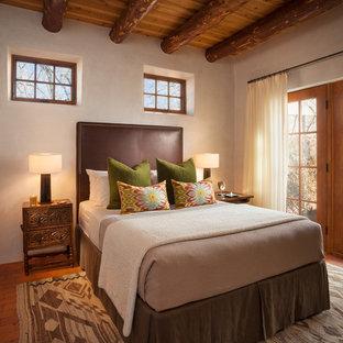 Foto de habitación de invitados de estilo americano, sin chimenea, con paredes beige y suelo de ladrillo