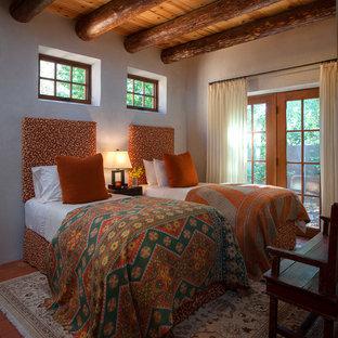 アルバカーキの中くらいのサンタフェスタイルのおしゃれな客用寝室 (ベージュの壁、レンガの床、暖炉なし) のインテリア