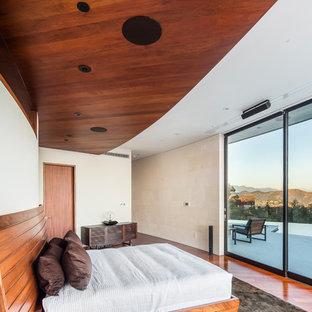 Imagen de dormitorio principal, contemporáneo, grande, sin chimenea, con paredes beige, suelo de madera en tonos medios y suelo rojo