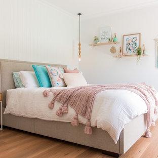 Beach style bedroom in Other with white walls, medium hardwood floors and beige floor.