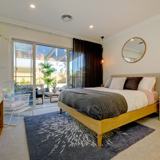 Design ideas for a beach style master bedroom in Central Coast with beige walls, carpet and beige floor.