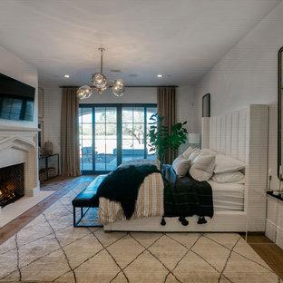 Imagen de dormitorio principal, contemporáneo, grande, con paredes grises, suelo de madera en tonos medios, chimenea tradicional, marco de chimenea de piedra y suelo marrón