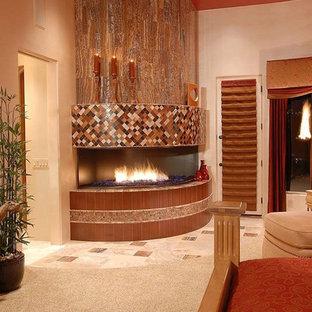 Modelo de dormitorio principal, mediterráneo, grande, con paredes beige, moqueta, chimenea de esquina, marco de chimenea de baldosas y/o azulejos y suelo gris