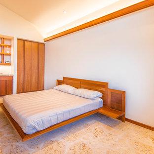 Exemple d'une grand chambre parentale rétro avec un mur beige, un sol en calcaire, une cheminée standard et un manteau de cheminée en pierre.