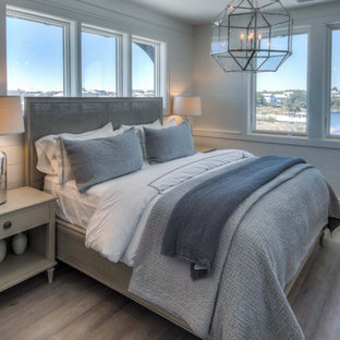 Example of a coastal guest light wood floor bedroom design in Miami with white walls