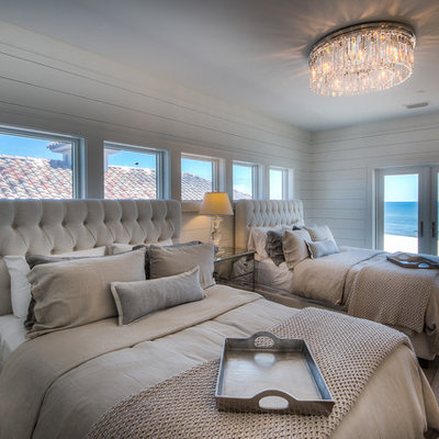 Example of a beach style guest light wood floor bedroom design in Miami with white walls