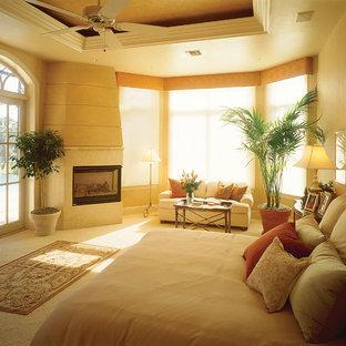 Diseño de dormitorio principal, mediterráneo, grande, con paredes beige, moqueta, chimenea tradicional y marco de chimenea de piedra