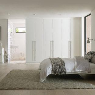 Ejemplo de habitación de invitados actual, de tamaño medio, con paredes blancas, suelo de madera clara y suelo gris