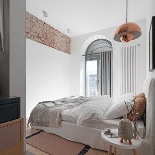 Photo of a scandinavian bedroom in Dorset with white walls, light hardwood flooring and beige floors.