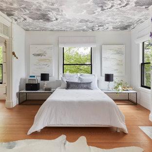 Modelo de dormitorio principal y papel pintado, actual, grande, con paredes blancas, suelo de madera clara, chimenea tradicional, marco de chimenea de piedra, suelo marrón y papel pintado