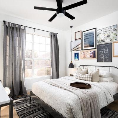 Example of a danish medium tone wood floor and brown floor bedroom design in Phoenix with white walls