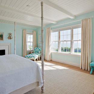 Modelo de dormitorio principal, marinero, grande, con paredes azules, suelo de madera en tonos medios, chimenea tradicional y marco de chimenea de ladrillo
